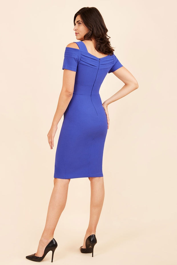 brunette model wearing diva catwalk amorette pencil skirt dress with a cold shoulder detaul and pleating across the bust and slit on a side of skirt in royal blue back