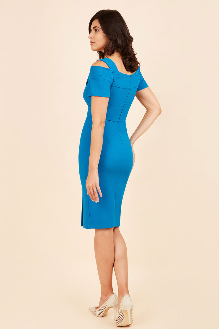 brunette model wearing diva catwalk amorette pencil skirt dress with a cold shoulder detaul and pleating across the bust and slit on a side of skirt in tropic teal back