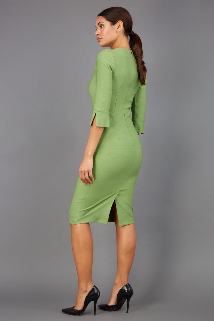 Brunette model is wearing couture stretch seed pencil bell 3/4 sleeve pencil dress by diva catwalk in citrus green back image