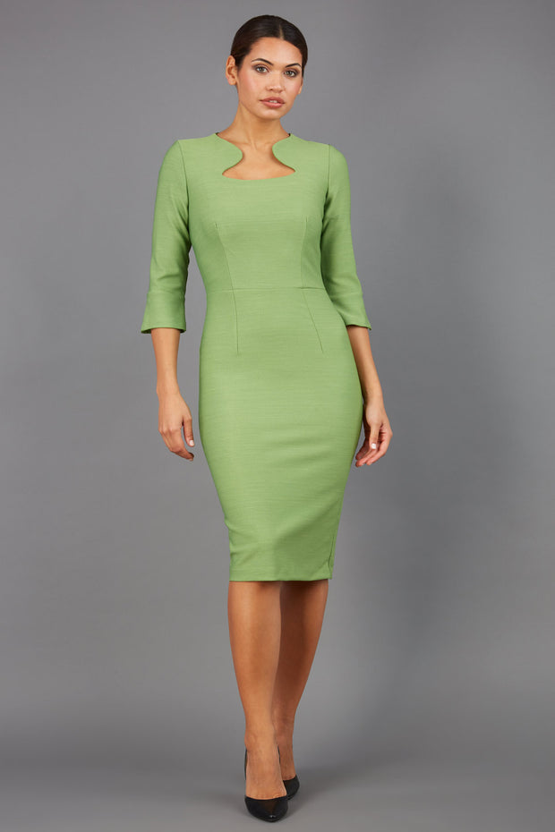 Brunette model is wearing couture stretch seed pencil bell 3/4 sleeve pencil dress by diva catwalk in citrus green front image