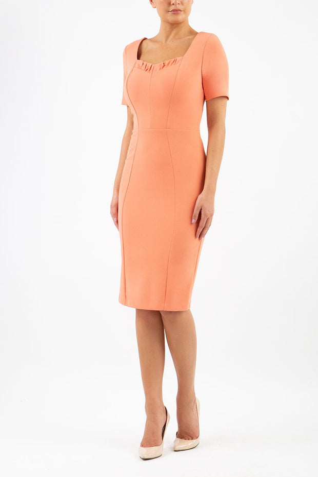 model wearing diva catwalk mitzi short sleeve pencil dress with square frilled neckline in dusty coral front