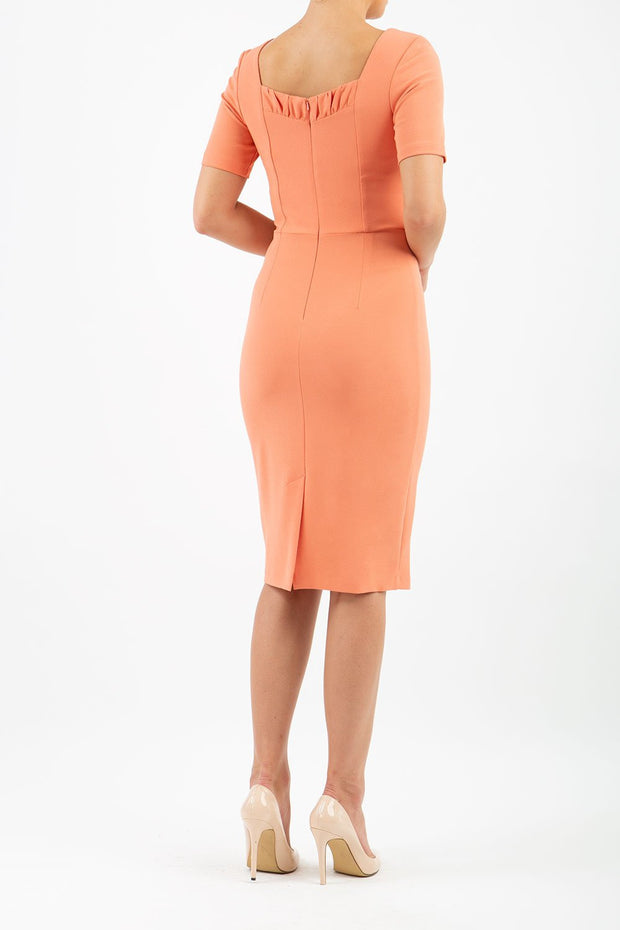 model wearing diva catwalk mitzi short sleeve pencil dress with square frilled neckline in dusty coral back