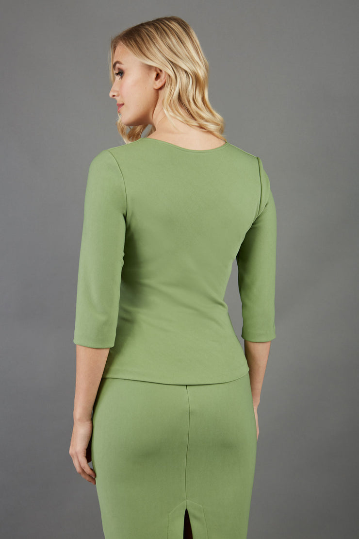 blonde model is wearing diva catwalk courtney sleeved topin colour aspen green back paired with green top