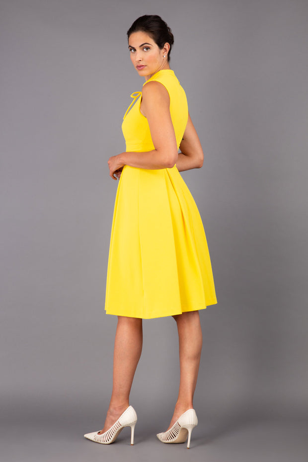 brunette model wearing diva catwalk oceana a-line swing skirt sleeveless dress with funnel neckline and tie detail in yellow back
