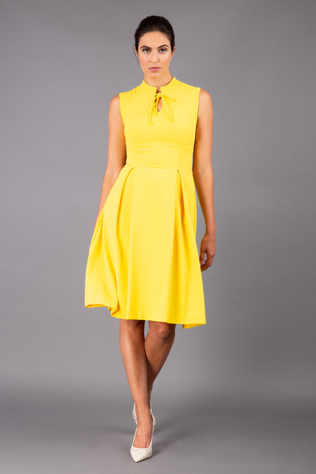 brunette model wearing diva catwalk oceana a-line swing skirt sleeveless dress with funnel neckline and tie detail in yellow front