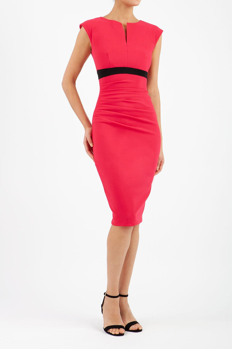 brunette model wearing diva catwalk nadia sleeveless pencil dress in raspberry pink colour with a contrasting black band and exposed zip at the back with a rounded neckline with a slit  in the middle front