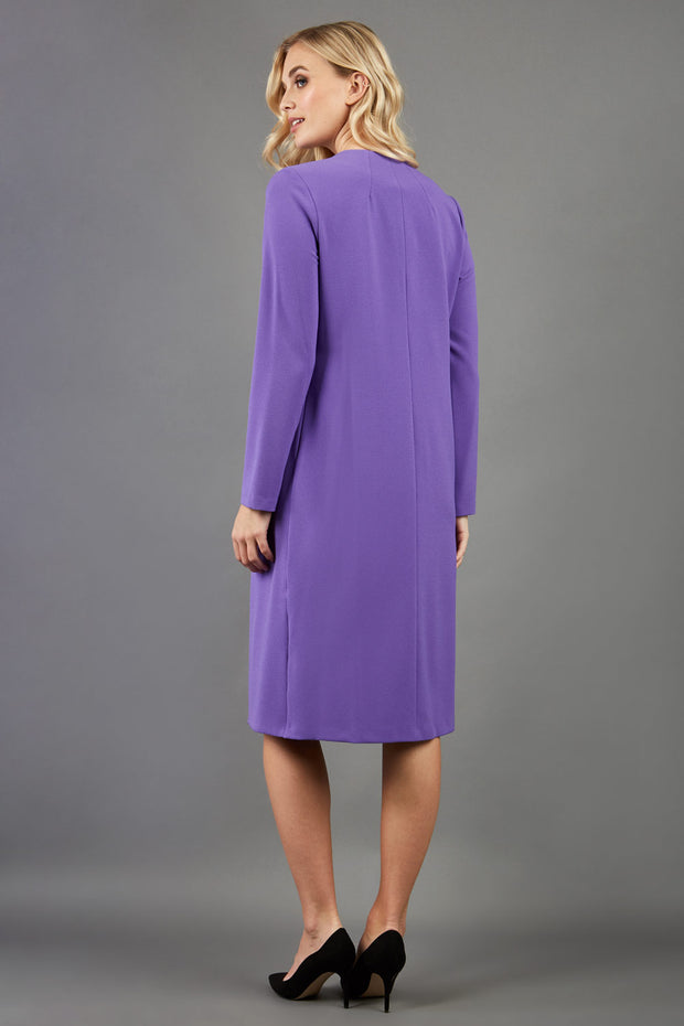 blonde model wearing the Diva Bliss Coat with round neckline in opulent violet back image