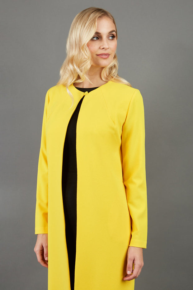 blonde model wearing the Diva Bliss Coat with round neckline in freesia yellow front image