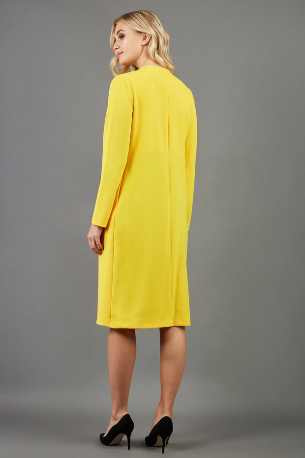 blonde model wearing the Diva Bliss Coat with round neckline in freesia yellow back image