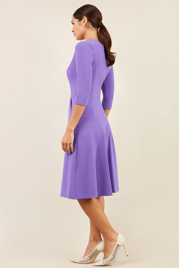 brunette model wearing diva catwalk waddeston swing a-line skirt dress with sleeves and pockets on side in colour opulent violet front