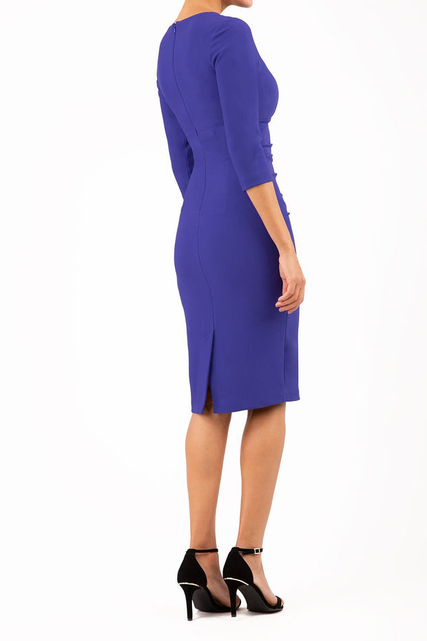 brunette model wearing diva catwalk best selling lydia pencil sleeved dress with slit at the neckline and pleating across the tummy in colour deep orient blue front