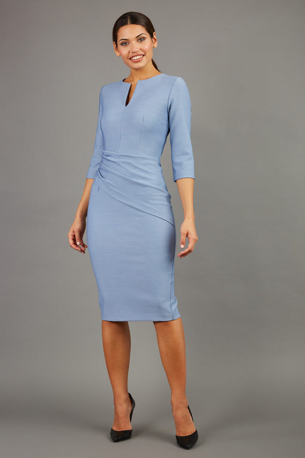 brunette model wearing seed diva catwalk milton sleeved pencil dress with a rounded neckline with a split in the middle in pale blue front