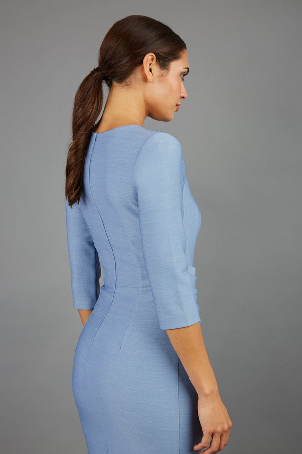 brunette model wearing seed diva catwalk milton sleeved pencil dress with a rounded neckline with a split in the middle in pale blue back