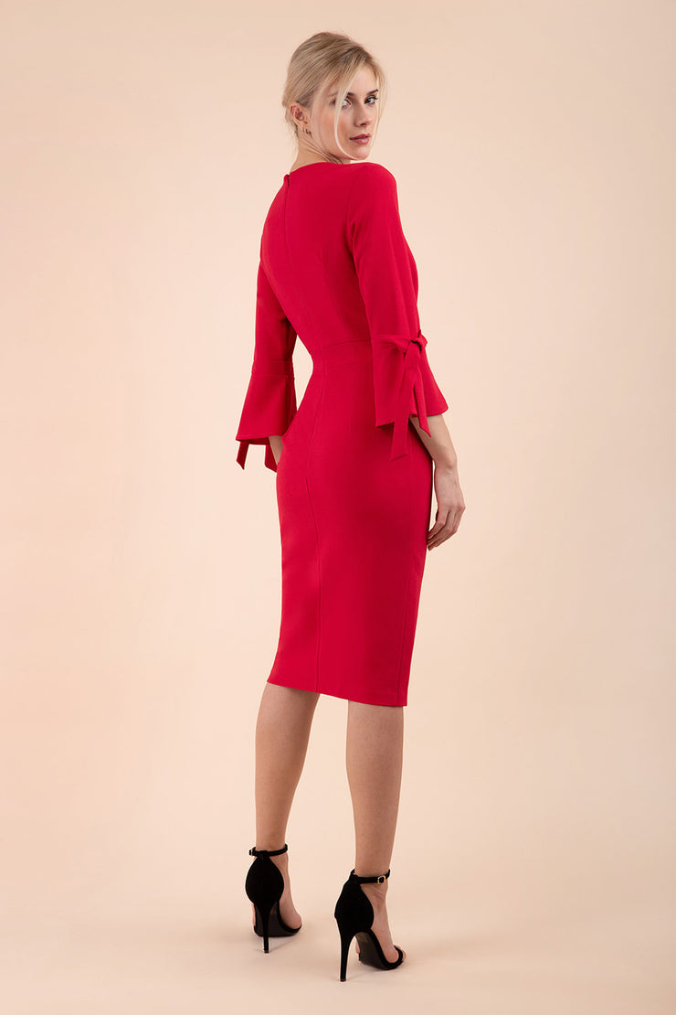 blonde model wearing diva catwalk zoe 3 4 sleeve formal dress with a split rounded neckline and split on skirt in ruby red colour back