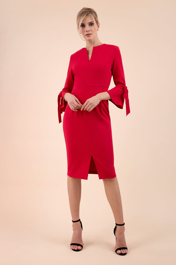 blonde model wearing diva catwalk zoe 3 4 sleeve formal dress with a split rounded neckline and split on skirt in ruby red colour front