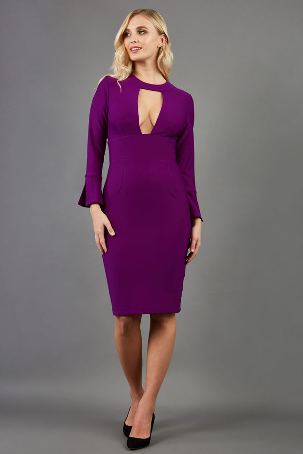 model is wearing diva catwalk fifi pencil skirt dress with three quarter flute sleeve and rounded neckline with a cut out at the front in purple  front image