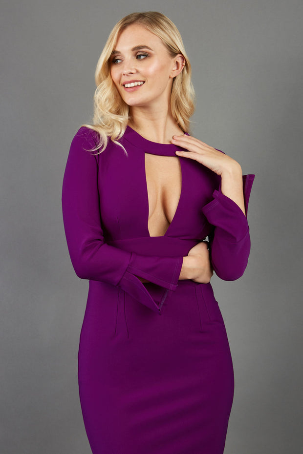 model is wearing diva catwalk fifi pencil skirt dress with three quarter flute sleeve and rounded neckline with a cut out at the front in purple
