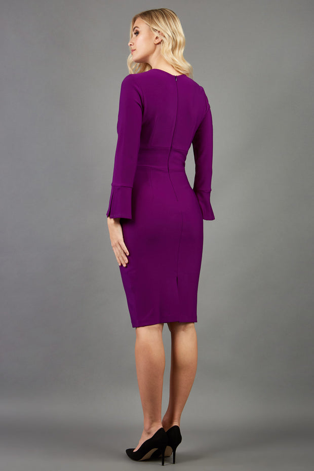 model is wearing diva catwalk fifi pencil skirt dress with three quarter flute sleeve and rounded neckline with a cut out at the front in purple  back image