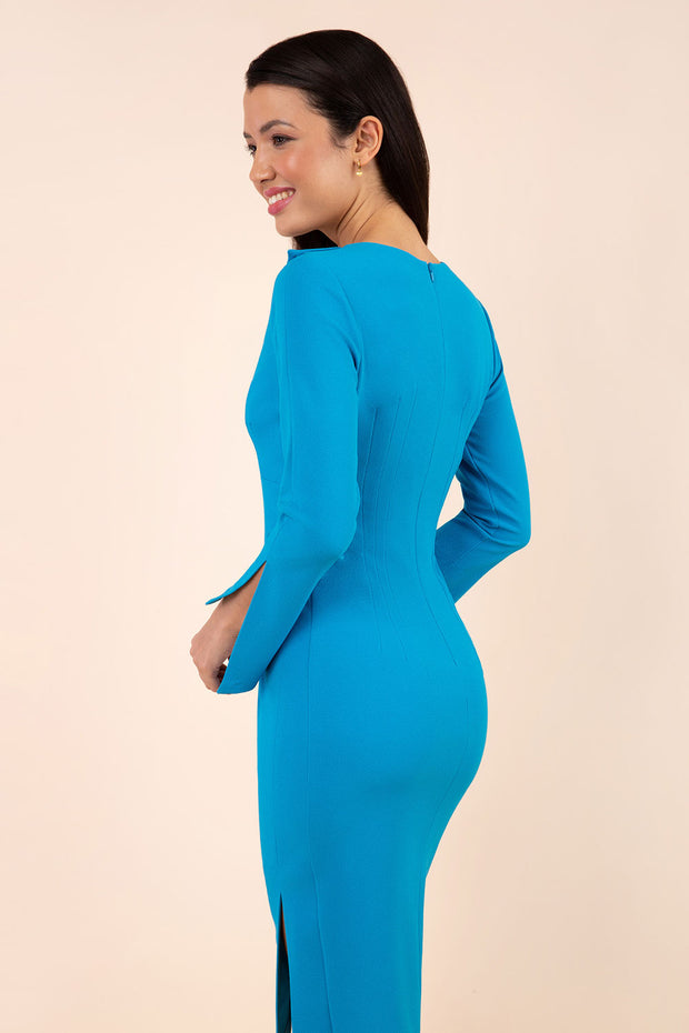 brunette model wearing diva catwalk chloe pencil skirt dress with long sleeves with deep slit and low v-neckline with tuxedo collar detailing in topaz colour front