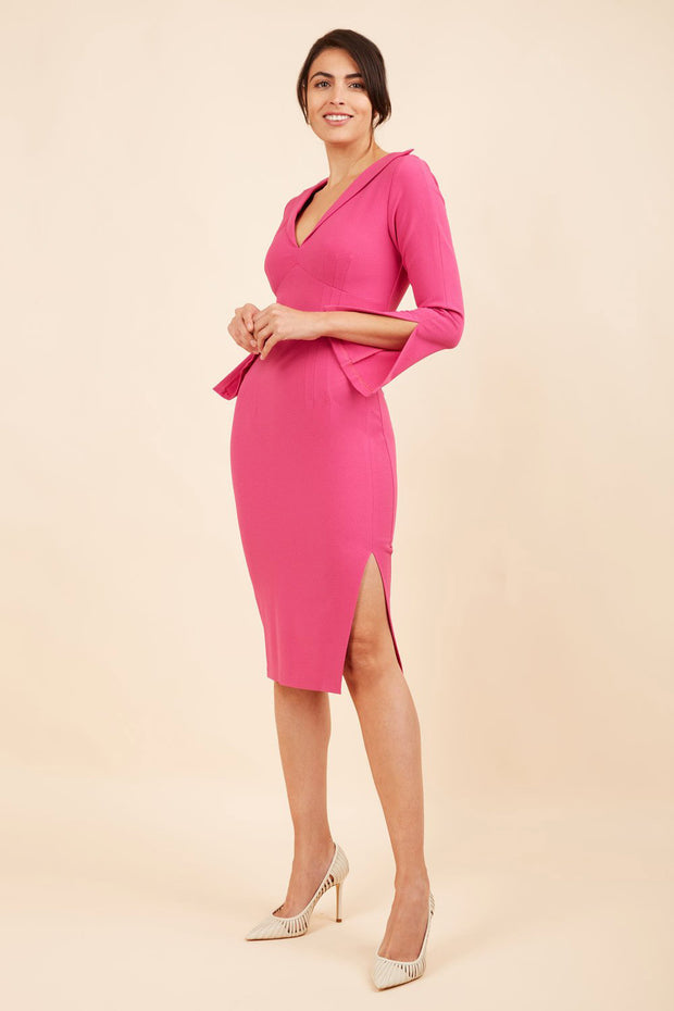 brunette model wearing diva catwalk chloe pencil skirt dress with long sleeves with deep slit and low v-neckline with tuxedo collar detailing in pink colour front