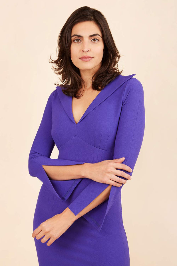 brunette model wearing diva catwalk chloe pencil skirt dress with long sleeves with deep slit and low v-neckline with tuxedo collar detailing in spectrum indigo colour front