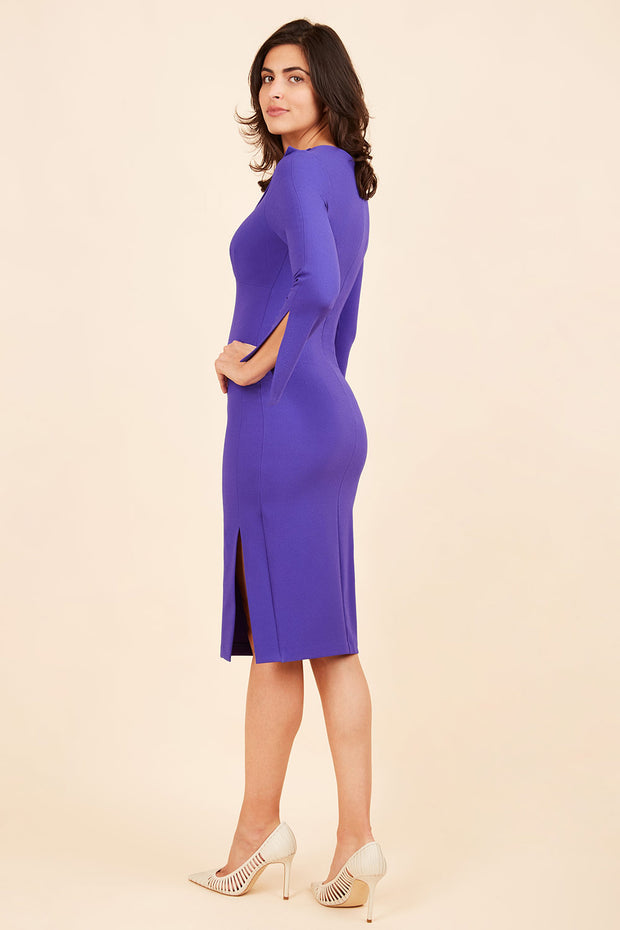 brunette model wearing diva catwalk chloe pencil skirt dress with long sleeves with deep slit and low v-neckline with tuxedo collar detailing in spectrum indogo colour front