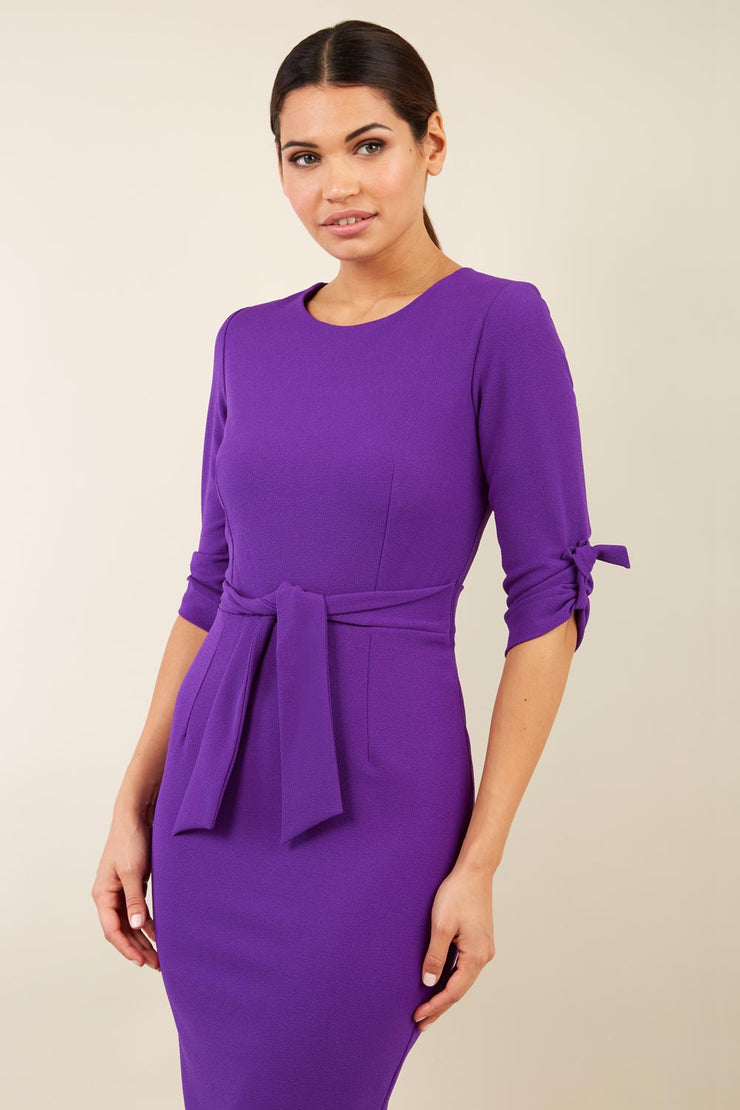 brunette model wearing diva catwalk tryst pencil purple dress with sleeves and belt detail at the front with rounded neckline front