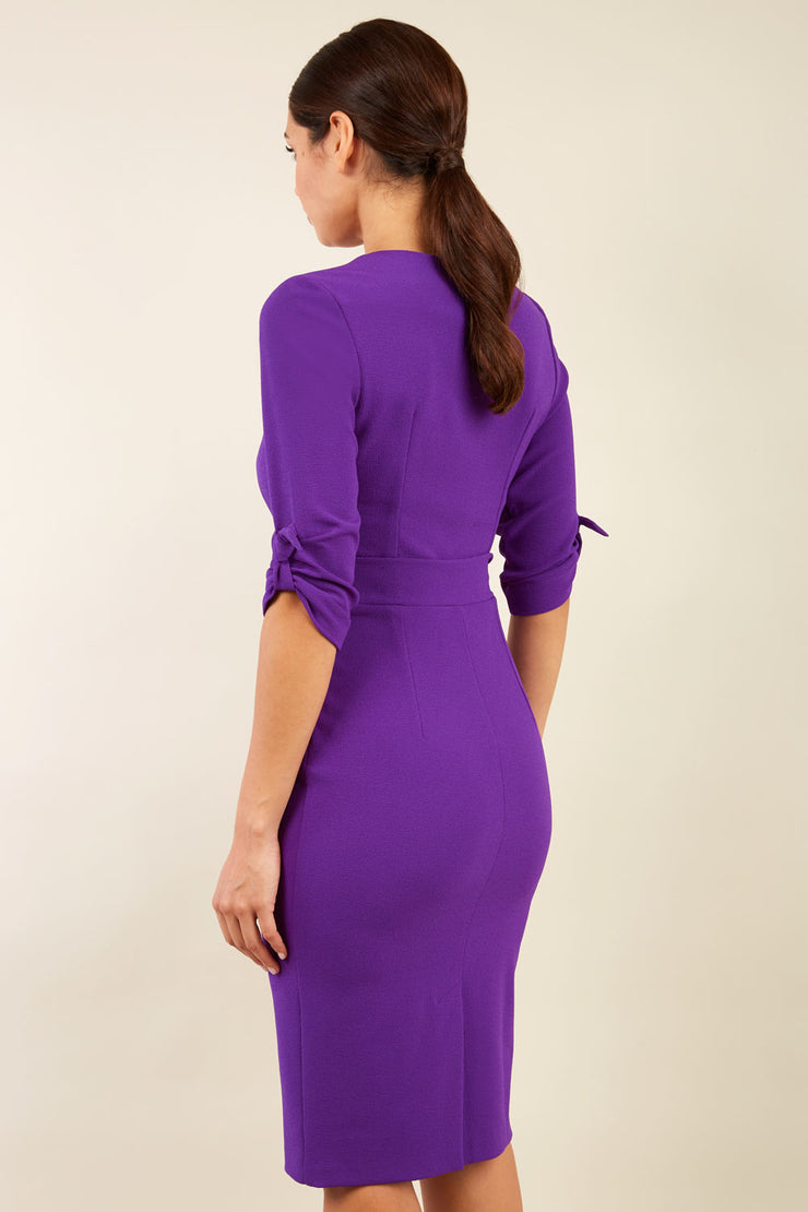 brunette model wearing diva catwalk tryst pencil purple dress with sleeves and belt detail at the front with rounded neckline back