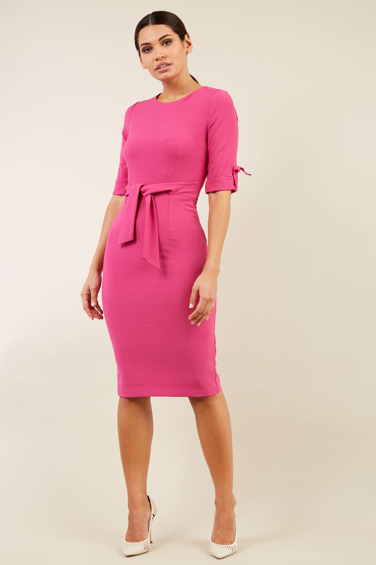 brunette model wearing diva catwalk tryst pencil pink dress with sleeves and belt detail at the front with rounded neckline front