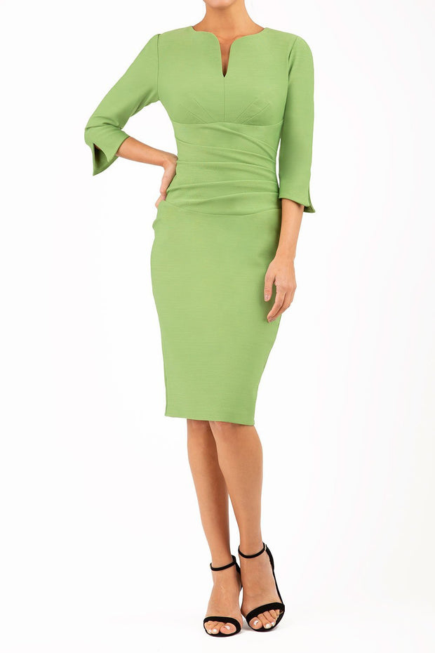 blonde model wearing seed tuscany pencil fitted dress in citrus green colour with a split in the neckline and split detail on sleeves front