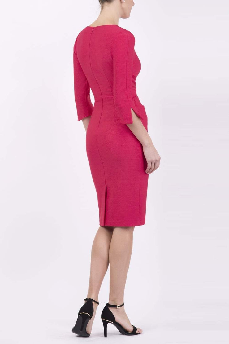 blonde model wearing seed tuscany pencil fitted dress in opera pink colour with a split in the neckline and split detail on sleeves back