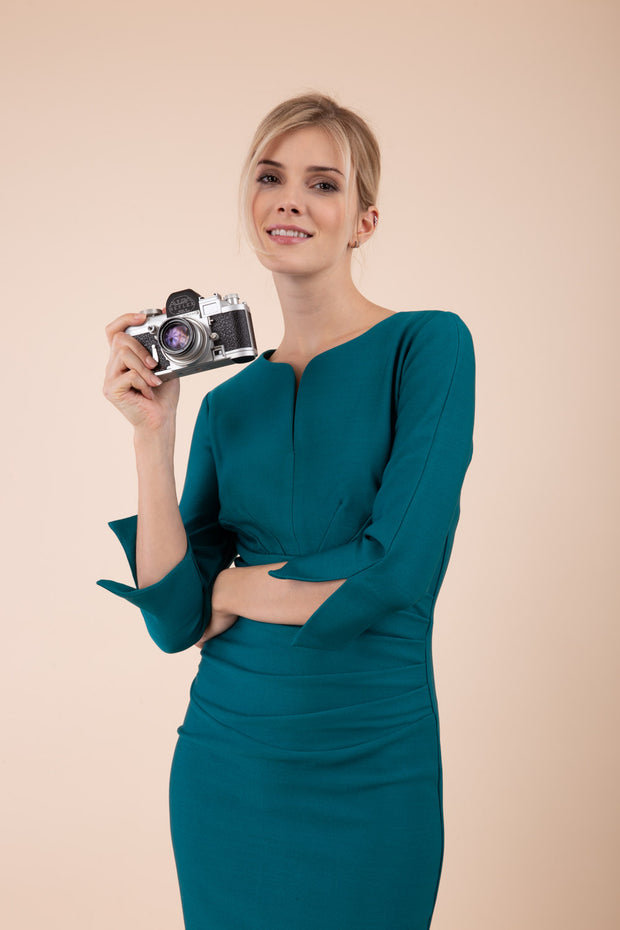blonde model wearing seed tuscany pencil fitted dress in pacific green colour with a split in the neckline and split detail on sleeves front