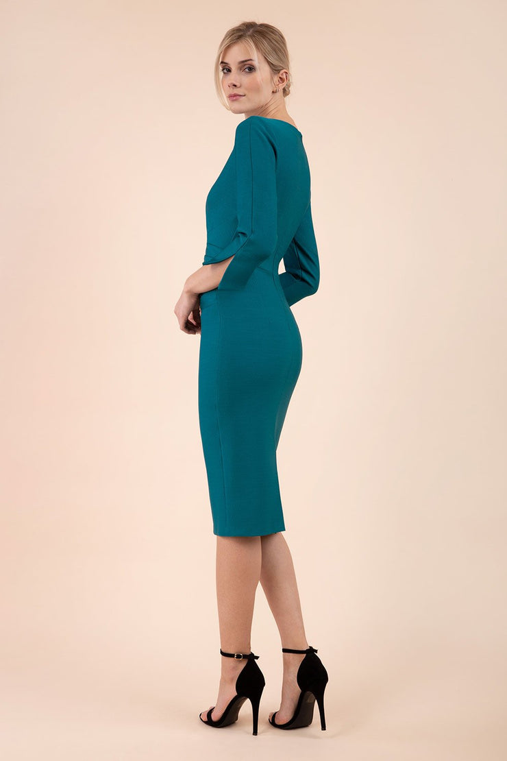 blonde model wearing seed tuscany pencil fitted dress in pacific green colour with a split in the neckline and split detail on sleeves back