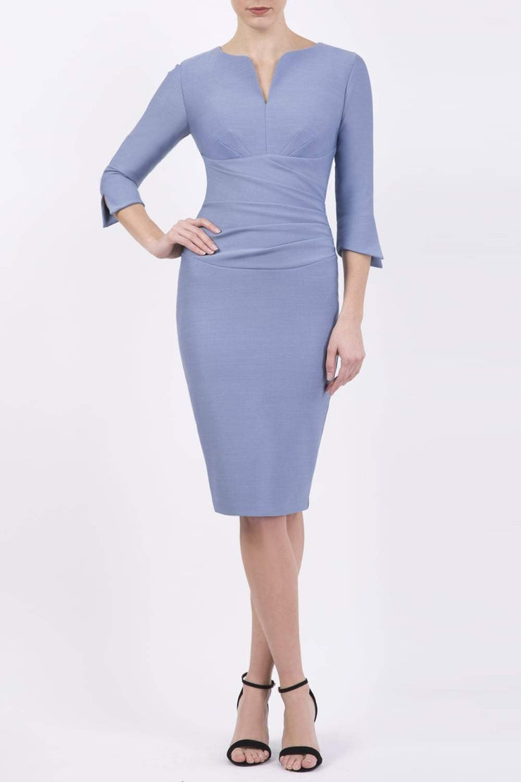 blonde model wearing seed tuscany pencil fitted dress in steel blue colour with a split in the neckline and split detail on sleeves front