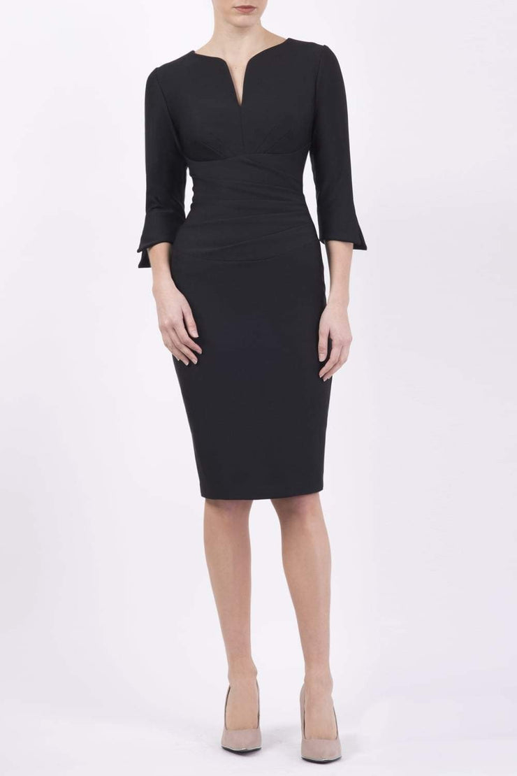 blonde model wearing seed tuscany pencil fitted dress in black colour with a split in the neckline and split detail on sleeves front