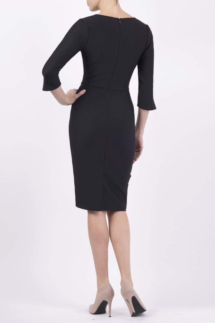 blonde model wearing seed tuscany pencil fitted dress in black colour with a split in the neckline and split detail on sleeves back
