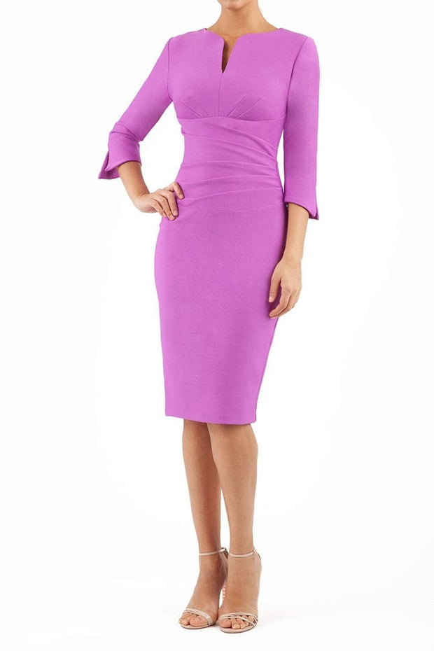 blonde model wearing seed tuscany pencil fitted dress in magenta mist colour with a split in the neckline and split detail on sleeves front