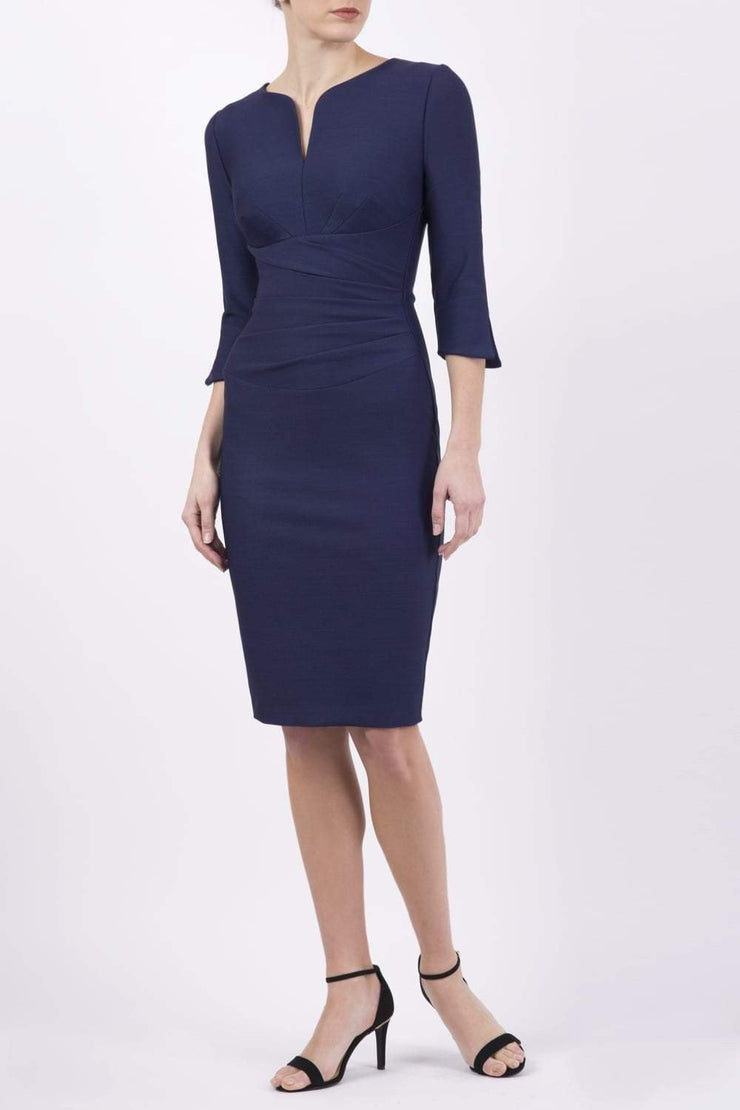 blonde model wearing seed tuscany pencil fitted dress in navy blue colour with a split in the neckline and split detail on sleeves front