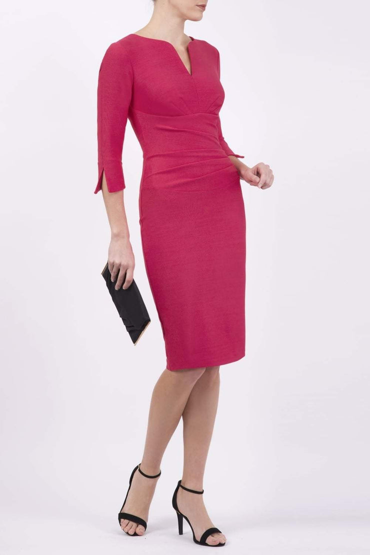 blonde model wearing seed tuscany pencil fitted dress in opera pink colour with a split in the neckline and split detail on sleeves front