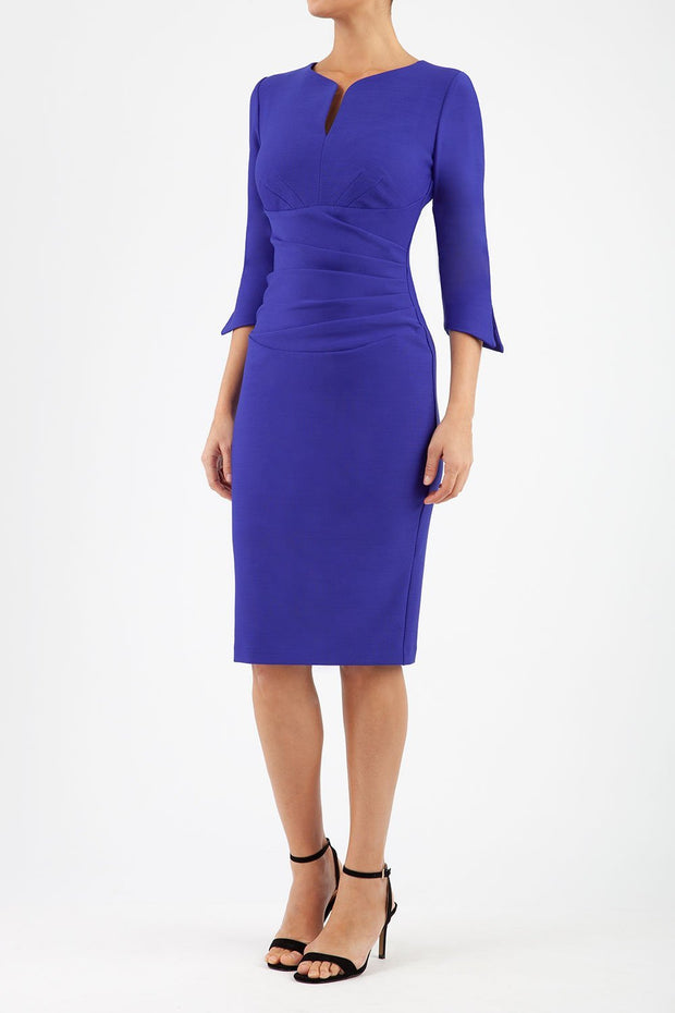 blonde model wearing seed tuscany pencil fitted dress in palace blue colour with a split in the neckline and split detail on sleeves front