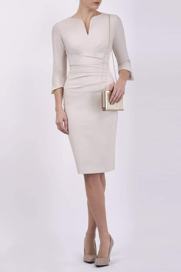 blonde model wearing seed tuscany pencil fitted dress in sandy cream colour with a split in the neckline and split detail on sleeves front