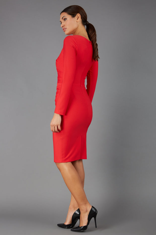 brunette model wearing diva catwalk pencil skirt dress sleeved with  pleating on side in electric red colour back