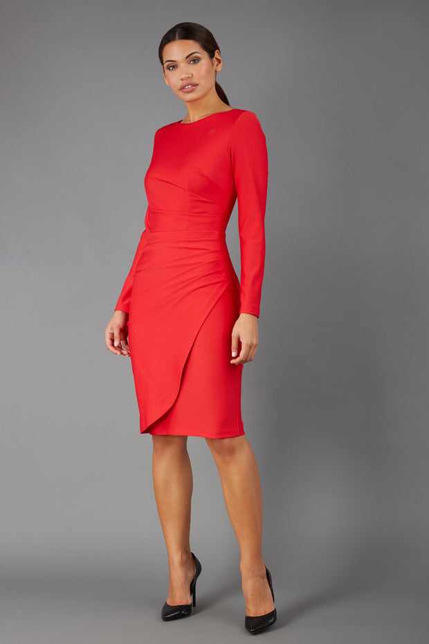 brunette model wearing diva catwalk pencil skirt dress sleeved with  pleating on side in electric red colour front