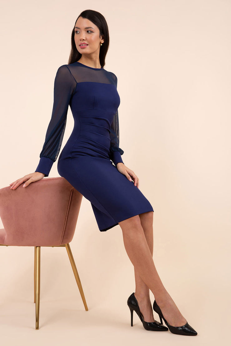 brunette model wearing diva catwalk navy pencil dress with long sleeves knee length and mesh detail sleeves front