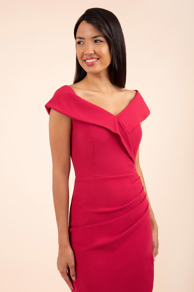 brunette model wearing diva catwalk evening pencil skirt dress sleeveless with lowered neckline and pleating on side in dazzle pink colour front