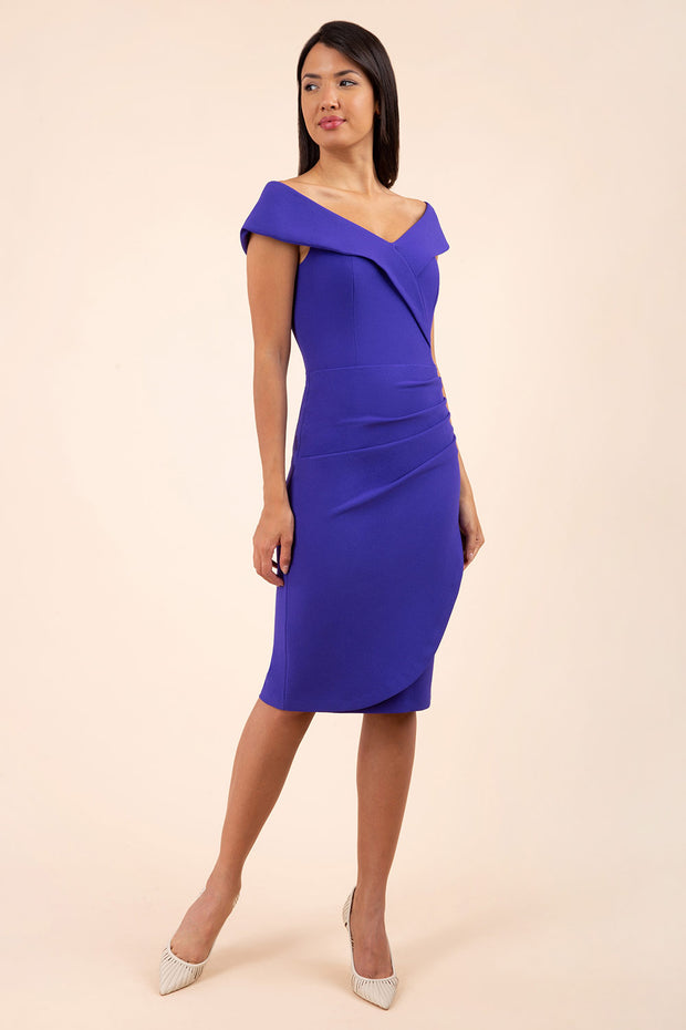 brunette model wearing diva catwalk pencil skirt dress sleeveless with lowered neckline and pleating on side in spectrum indigo colour front