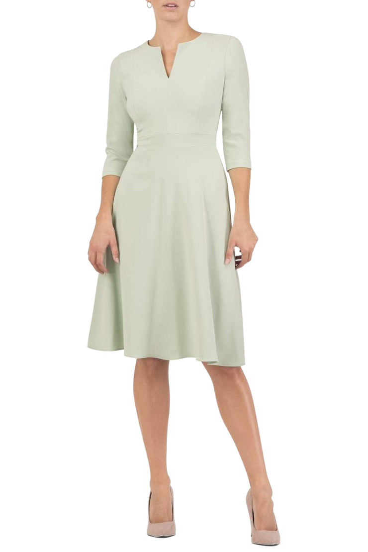 blonde model wearing diva catwalk romney three quarter sleeve swing dress with a band in deco green front
