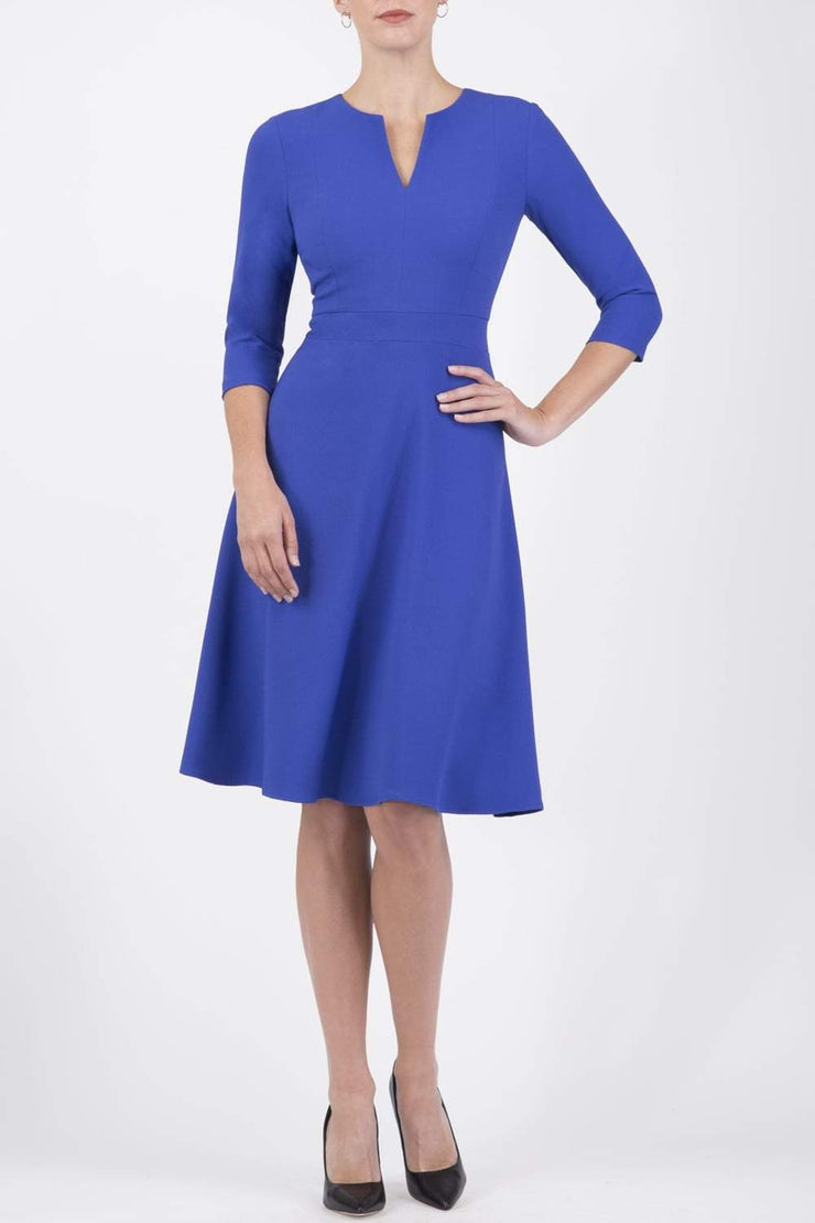 blonde model wearing diva catwalk romney three quarter sleeve swing dress with a band in riviera blue front