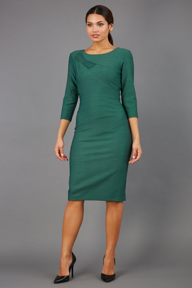 brunette model wearing diva catwalk couture althorp pencil fitted dress with sleeves and rounded neckline and bow detail at the top in chrome green colour front