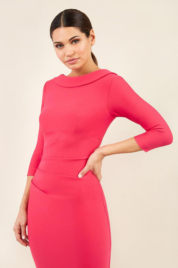 model wearing diva catwalk york pencil-skirt dress with sleeves and rounded folded collar and plearing across the tummy area in yarrow pink colour front